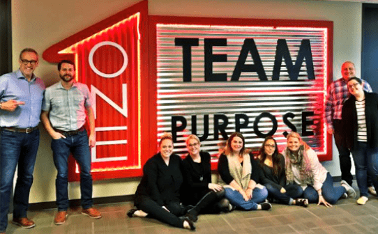 PrimeLending employees sitting and standing in front of a sign that says one team one purpose
